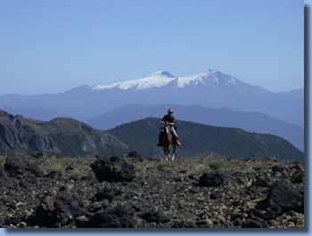 Rider in front of Villarrica on the crossing the Andes on Horseback in Northern patagonia