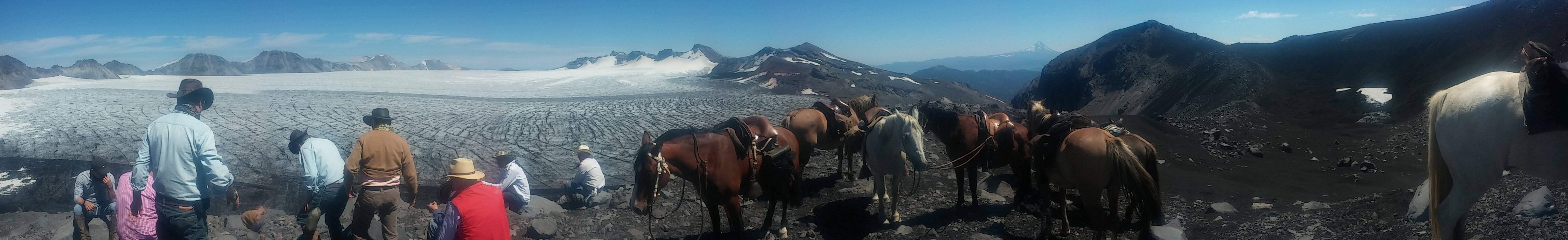 Riders and horses in front of the crater of Sollipulli